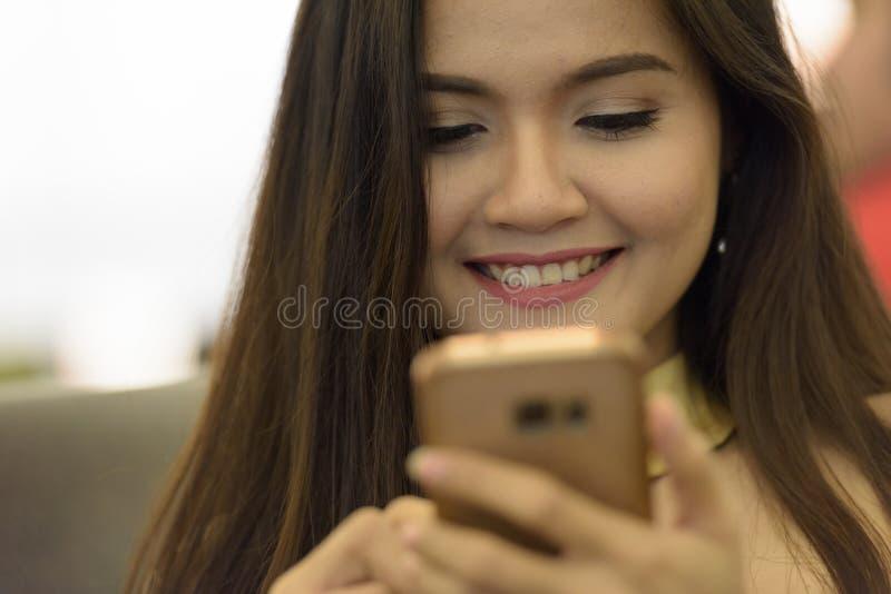 Giovane donna asiatica felice che sorride mentre usa il cellulare immagini stock