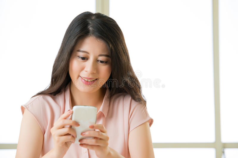 Giovane donna asiatica felice che usando invio di messaggi di testo dello Smart Phone fotografia stock libera da diritti