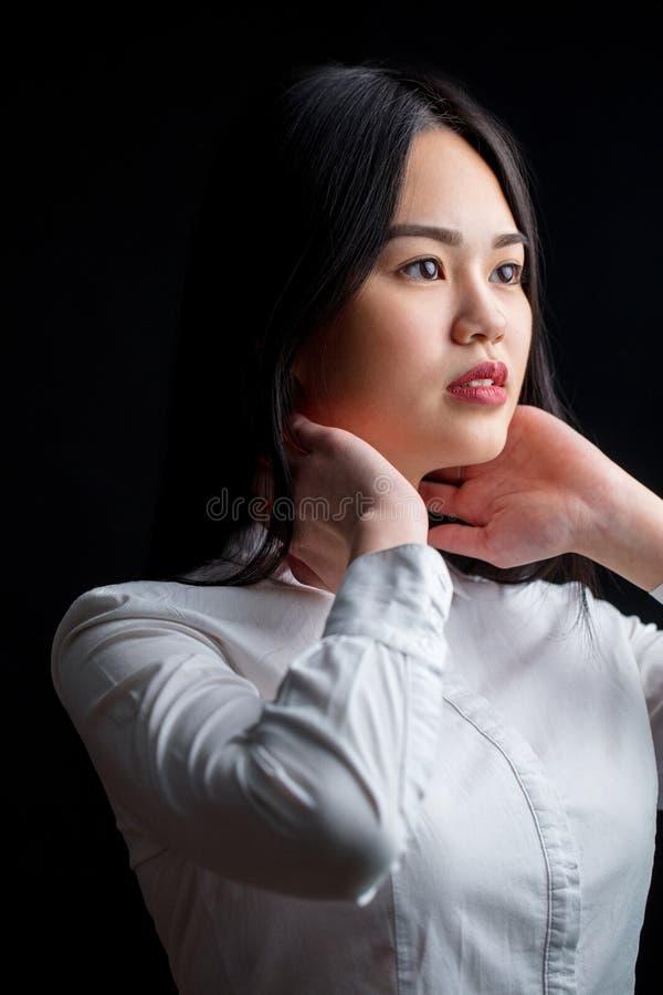 Giovane donna asiatica nel bianco sopra fondo nero Il nero e briciolo fotografia stock