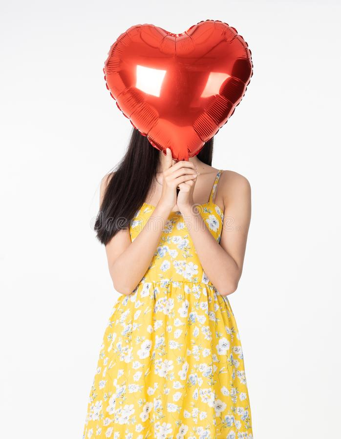 Giovane donna asiatica nel cuore rosso del pallone della tenuta gialla del vestito Giovane donna che lo tiene con essere eccitato fotografia stock libera da diritti