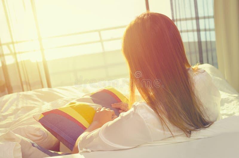 Giovane donna asiatica in pigiami che si siedono e che si rilassano sul letto immagini stock libere da diritti