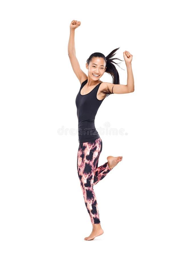 Giovane donna asiatica sorridente allegra nel dancing degli abiti sportivi immagini stock libere da diritti