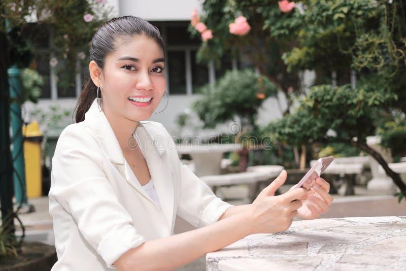 Giovane donna asiatica sorridente che per mezzo dello Smart Phone mobile Internet del concetto di cose fotografie stock