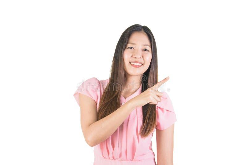 Giovane donna asiatica sorridente con il punto del dito al lato fotografie stock