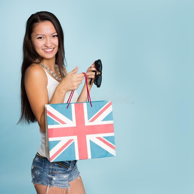 Giovane donna asiatica sorridente felice con il sacchetto della spesa immagini stock
