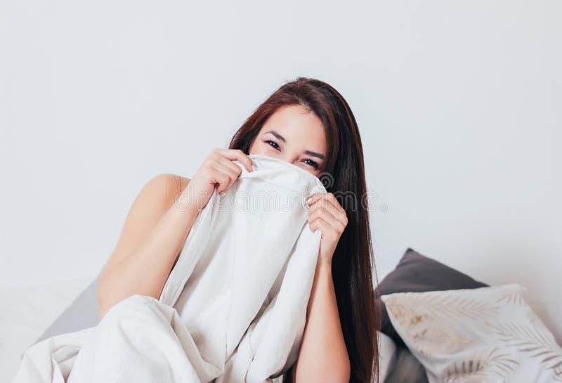 Giovane donna asiatica sorridente felice della ragazza dei bei capelli lunghi che si riposa a letto, mattina accogliente fotografie stock
