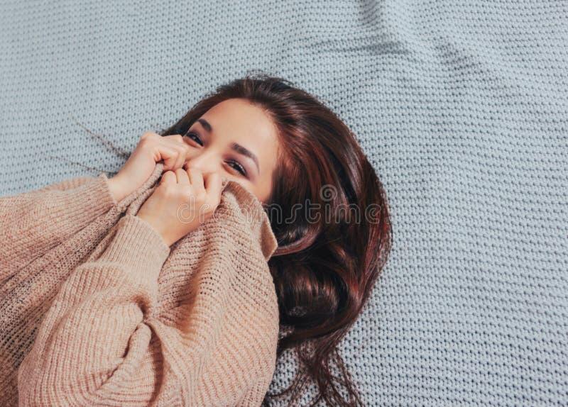 Giovane donna asiatica sorridente felice della ragazza dei bei capelli lunghi in maglione beige accogliente che si trova sulla co fotografia stock libera da diritti