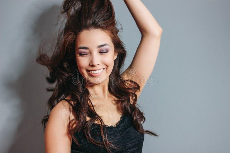 Giovane donna asiatica sorridente sensuale felice con capelli ricci lunghi scuri sul fondo grigio della parete Ragazza divertendo immagini stock