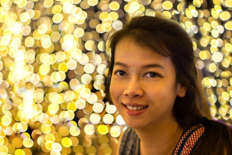 Giovane donna asiatica sul fondo delle luci del bokeh immagine stock libera da diritti