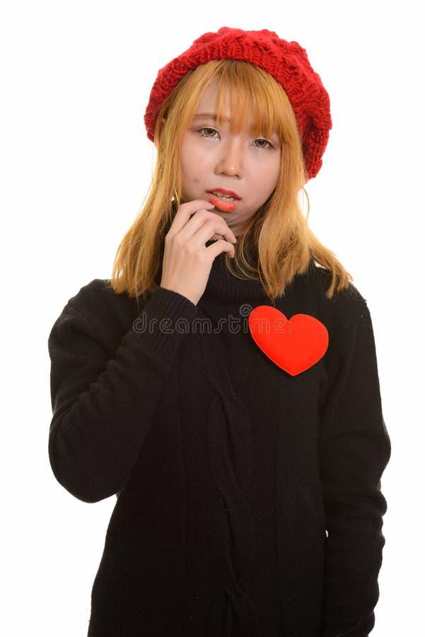 Giovane donna asiatica sveglia con cuore rosso sul petto fotografia stock libera da diritti