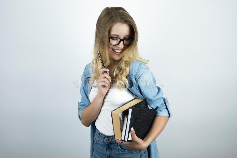 Giovane donna astuta bionda in vetri che tengono i libri ed il fondo bianco della penna immagini stock libere da diritti