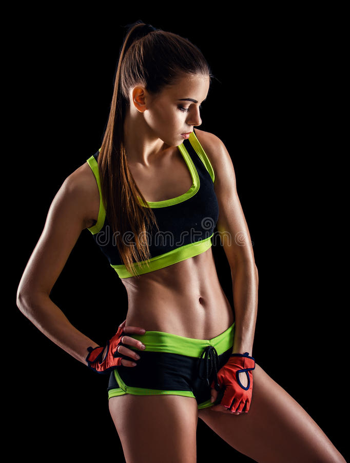 Giovane donna atletica in abiti sportivi che posano nello studio contro il fondo nero Figura femminile ideale di sport immagine stock libera da diritti