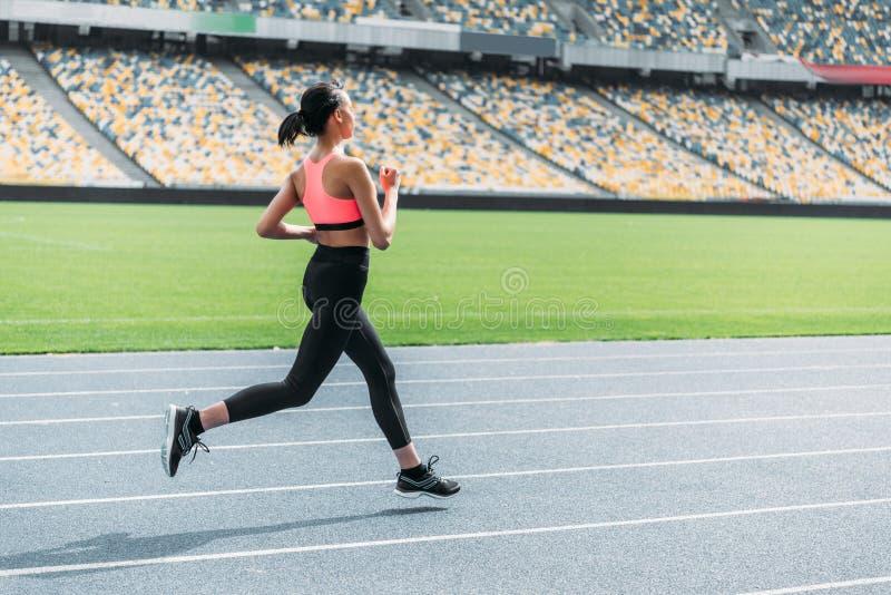Giovane donna atletica in abiti sportivi che sprinta sullo stadio corrente della pista fotografia stock libera da diritti