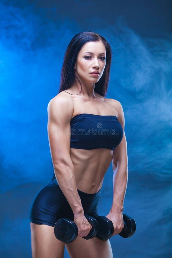 Giovane donna atletica che fa un allenamento di forma fisica con le teste di legno sul fondo nero dello studio Intorno agli scher fotografia stock