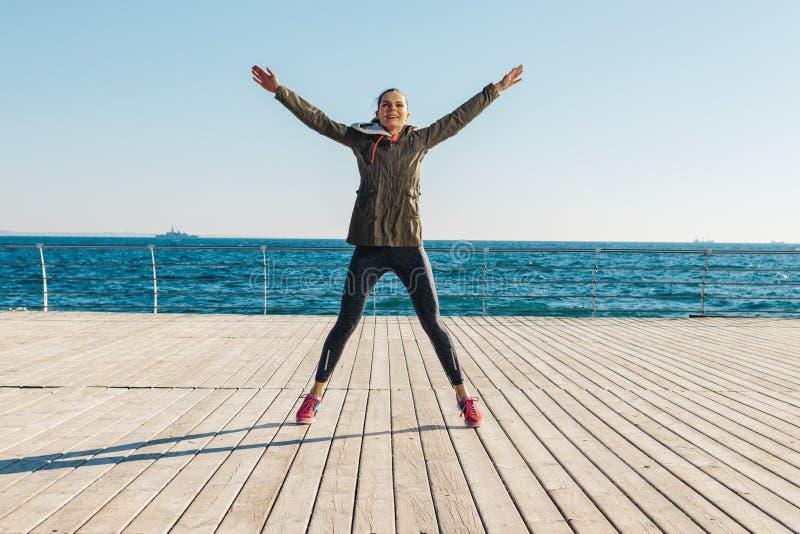 Giovane donna atletica che salta sulla spiaggia immagini stock libere da diritti