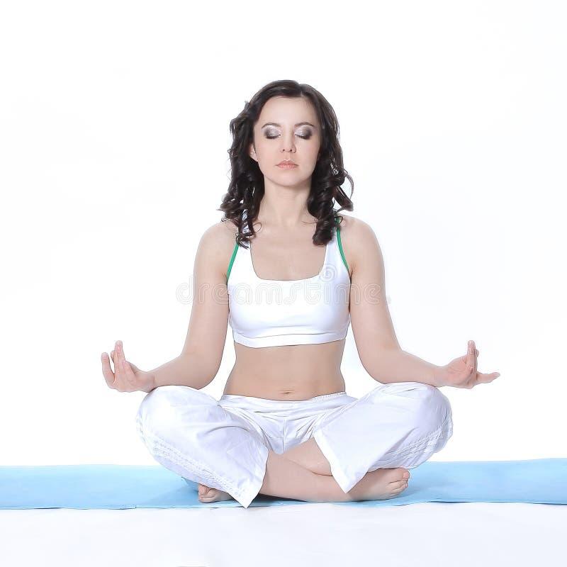 Giovane donna atletica che si siede nella posa di Lotus Isolato su bianco fotografie stock libere da diritti
