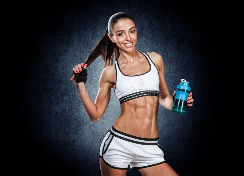 Giovane donna atletica con la bottiglia di acqua a disposizione su un backgr nero fotografie stock libere da diritti