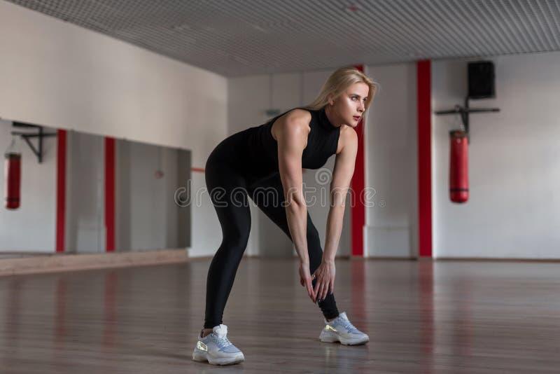 Giovane donna atletica esile in vestiti alla moda neri sportivi su un addestramento nella palestra La ragazza attraente fa gli es immagine stock