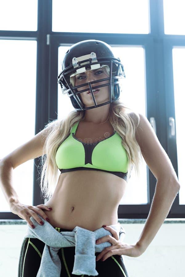 giovane donna atletica nel reggiseno di sport e nello sguardo del casco di football americano immagini stock libere da diritti