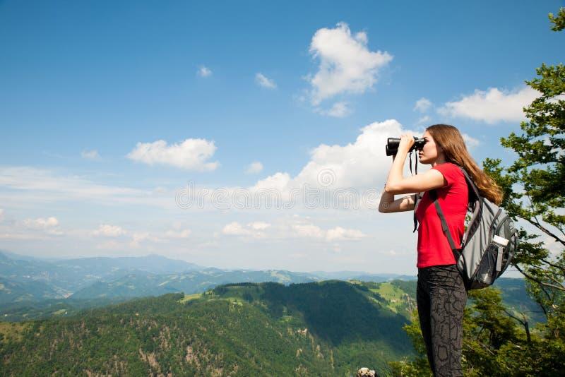 Giovane donna attiva che guarda un paesaggio della montagna con il binocolo fotografie stock libere da diritti