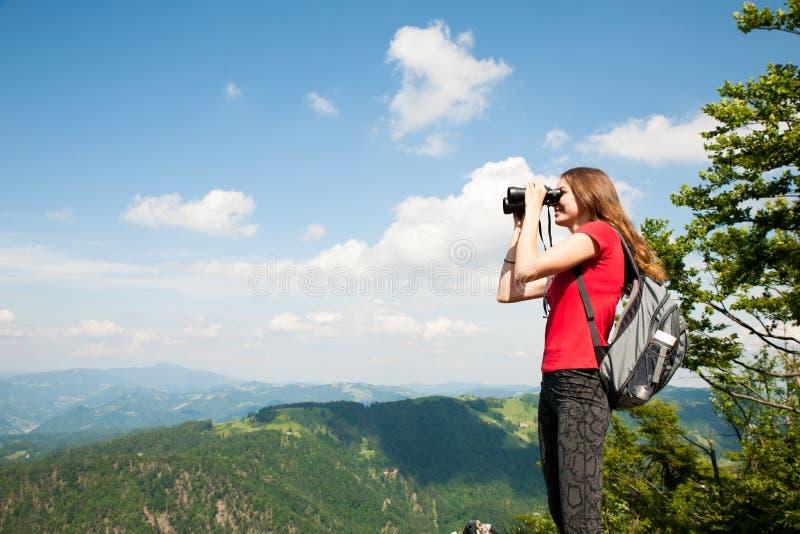 Giovane donna attiva che guarda un paesaggio della montagna con il binocolo fotografia stock libera da diritti