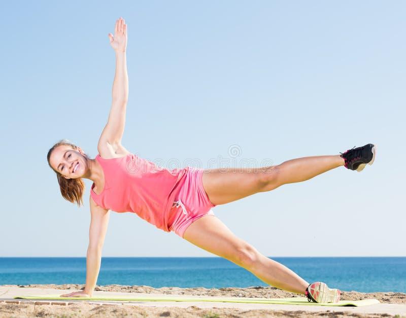 Giovane donna attiva che si esercita sulla stuoia di esercizio all'aperto fotografia stock libera da diritti