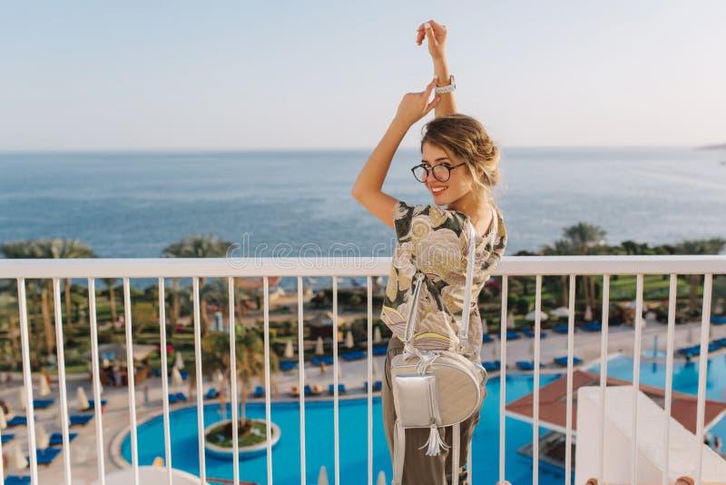 Giovane donna attraente, abbastanza turistica sulla vacanza, festa Goda della vista sul mare, oceano sul balcone in hotel Bello fotografia stock
