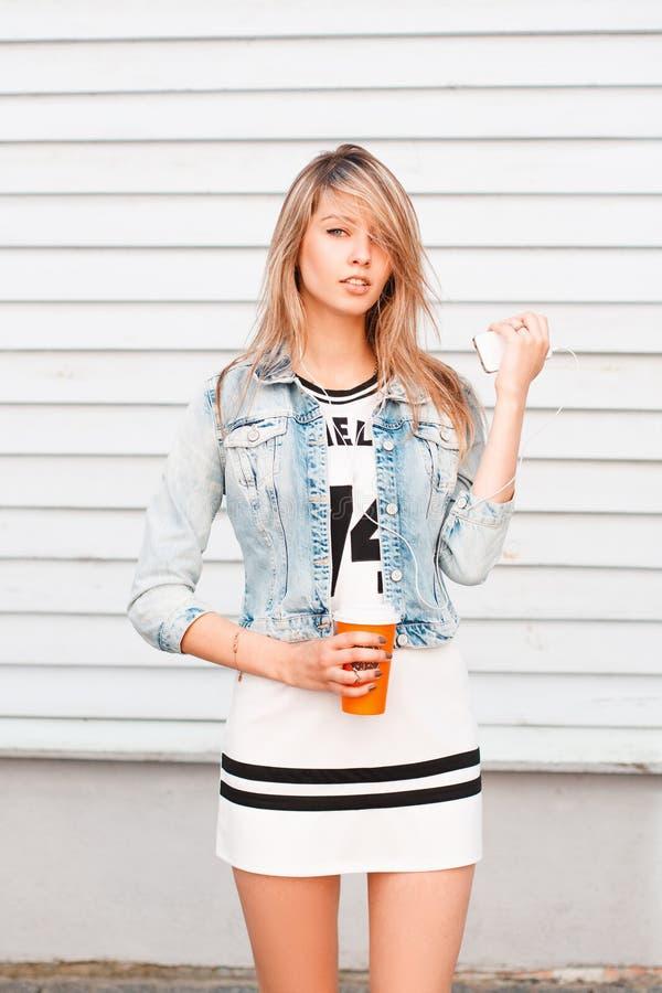 Giovane donna attraente alla moda in rivestimento d'avanguardia del jesh in vestito bianco con le pose nere del modello vicino al fotografia stock