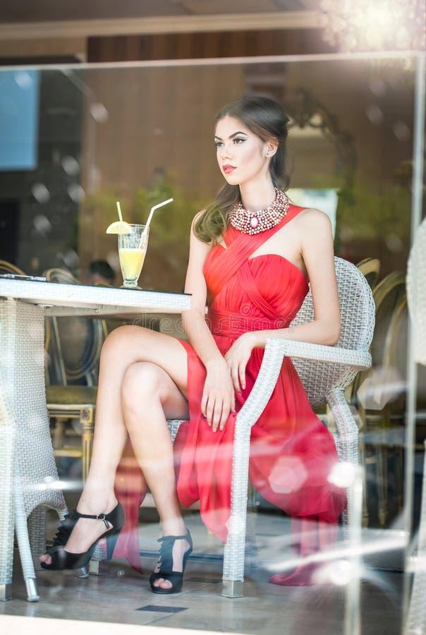 Giovane donna attraente alla moda in vestito rosso che si siede nel ristorante, oltre le finestre Bella posa castana nel ristoran fotografie stock