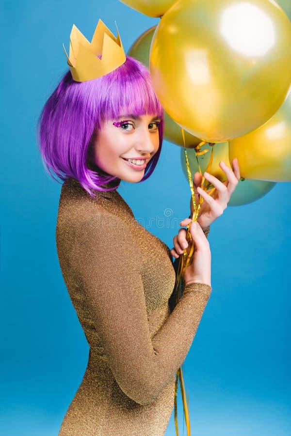 Giovane donna attraente allegra con capelli porpora tagliati divertendosi con i palloni dorati su fondo blu Corona sulla testa fotografia stock libera da diritti