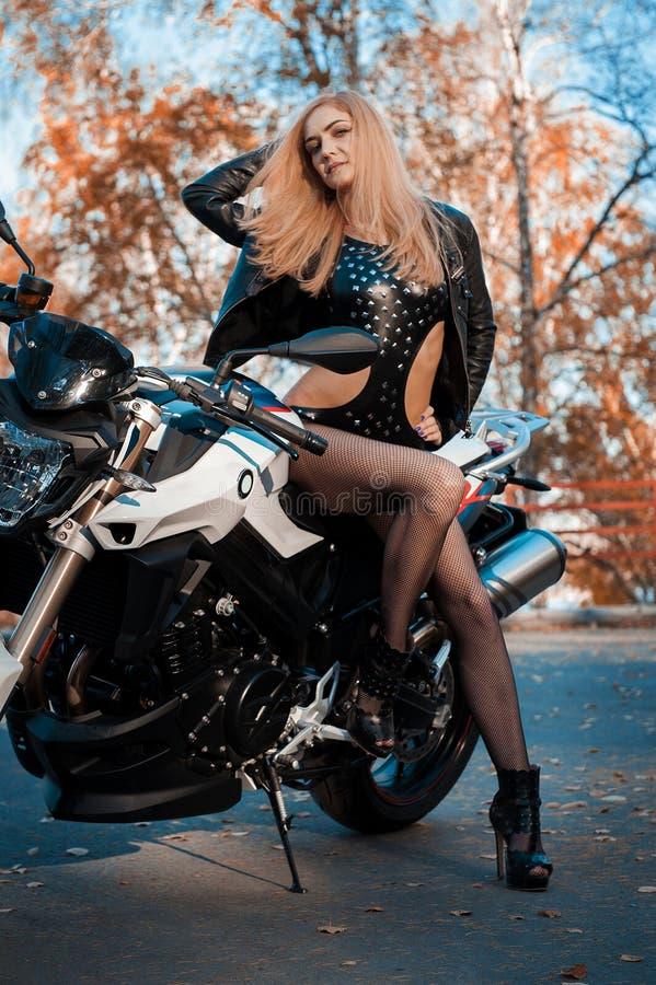 Giovane donna attraente in attrezzatura di cuoio nera con il motociclo classico di stile fotografia stock