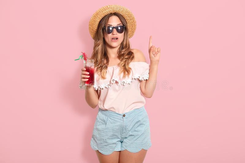 Giovane donna attraente in attrezzatura di estate su fondo rosa Ragazza felice in occhiali da sole che posano con il cappello ed  immagini stock
