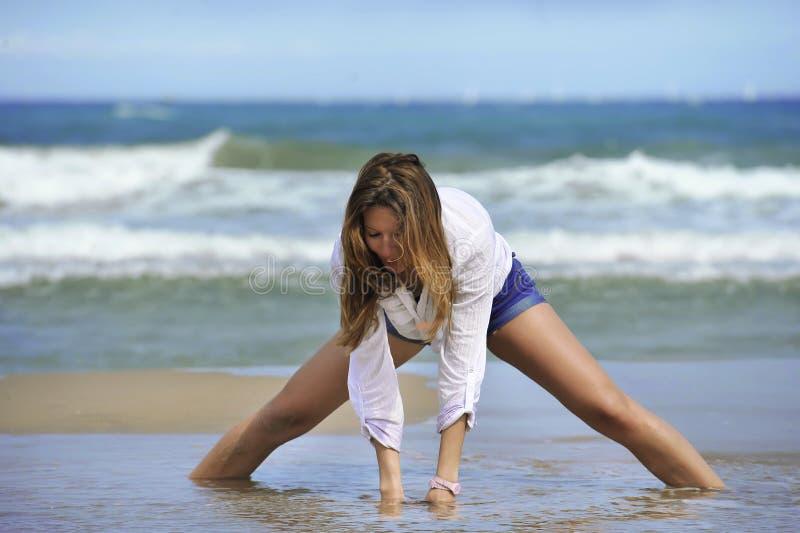 Giovane donna attraente in breve e camicia che gioca con la sabbia sulla spiaggia con il mare su lei indietro fotografia stock libera da diritti