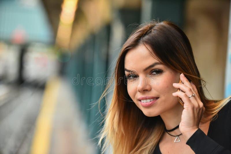 Giovane donna attraente che discute a fondo il telefono sul binario del treno fotografia stock libera da diritti