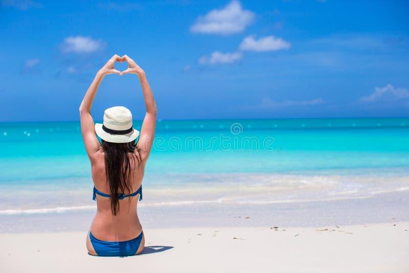 Giovane donna attraente che fa un cuore con le mani sulla spiaggia immagine stock