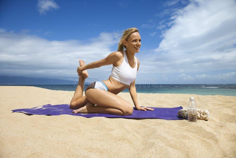 Giovane donna attraente che fa yoga sulla spiaggia fotografia stock libera da diritti