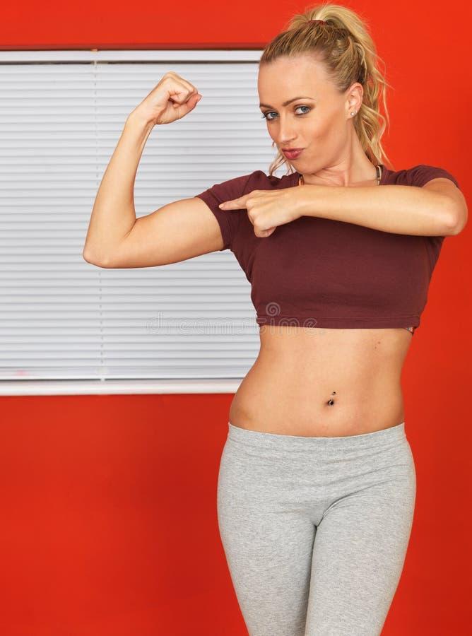 Giovane donna attraente che flette i suoi muscoli ed indicare del braccio fotografie stock libere da diritti