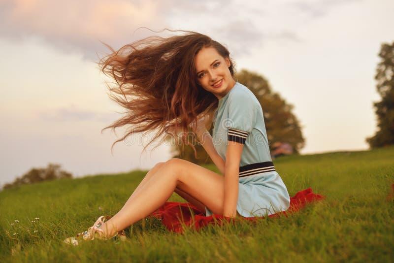 Giovane donna attraente che gode del suo tempo fuori nel parco di tramonto Ragazza di modello con la posa lunga magnifica dei cap fotografie stock