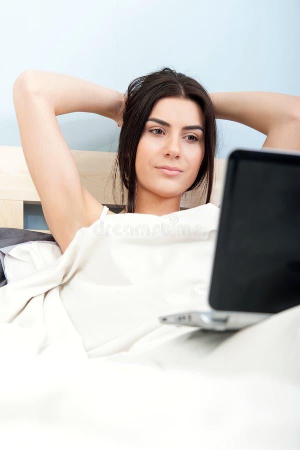 Giovane donna attraente che guarda un film sul computer portatile fotografie stock