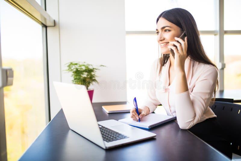Giovane donna attraente che parla sul telefono cellulare e che sorride mentre sedendosi al suo posto di lavoro in ufficio ed esam fotografia stock