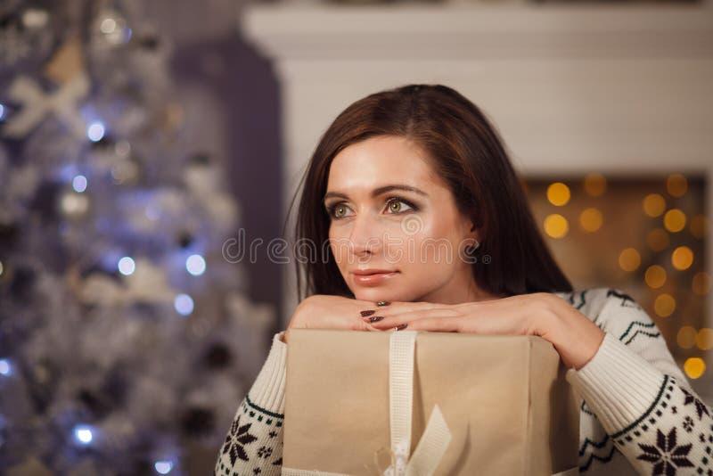Giovane donna attraente che pensa vicino all'albero di Natale fotografie stock