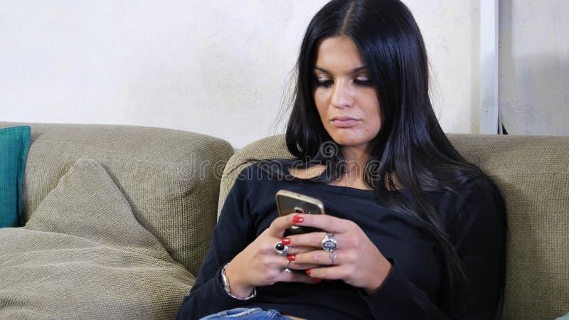 Giovane donna attraente che per mezzo del telefono cellulare sullo strato fotografie stock libere da diritti