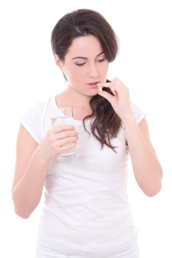 Giovane donna attraente che prende pillola isolata su bianco immagini stock