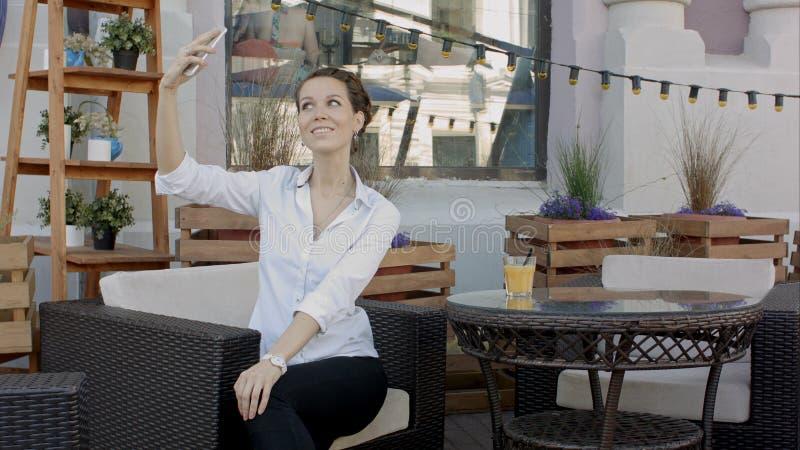Giovane donna attraente che prende un autoritratto sul suo telefono cellulare, all'aperto fotografia stock