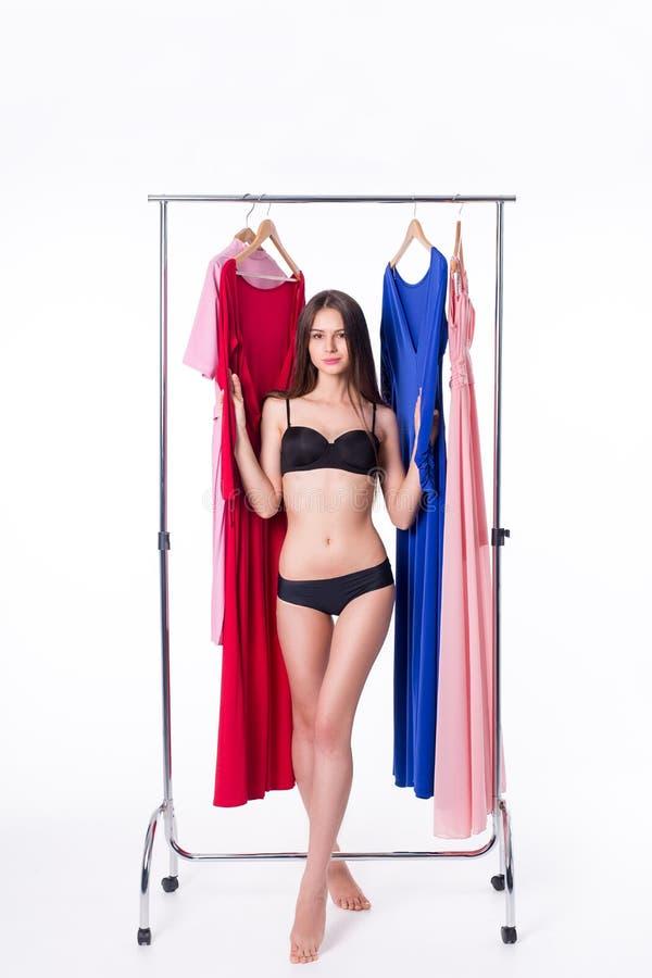 Giovane donna attraente che prova a scegliere vestito Isolato su bianco fotografia stock libera da diritti