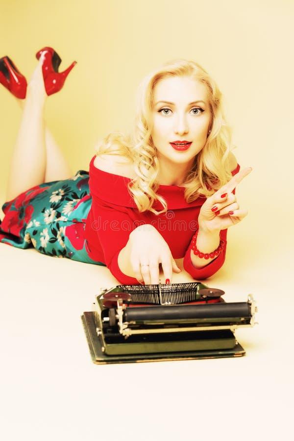 Giovane donna attraente che scrive su una macchina da scrivere fotografia stock libera da diritti