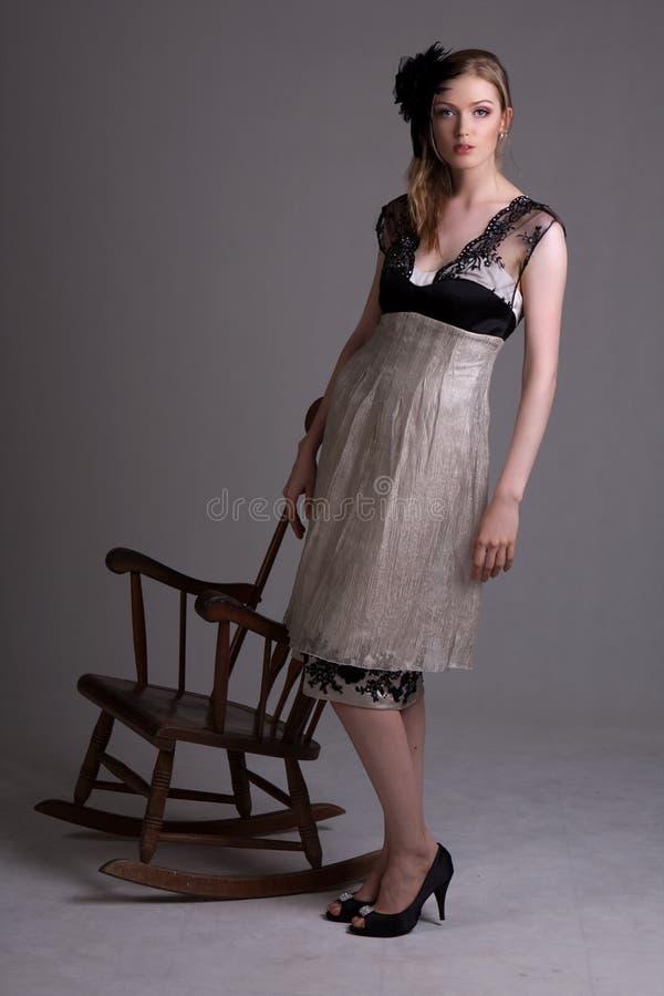 Giovane donna attraente che si leva in piedi al lato di una C d'oscillazione immagini stock
