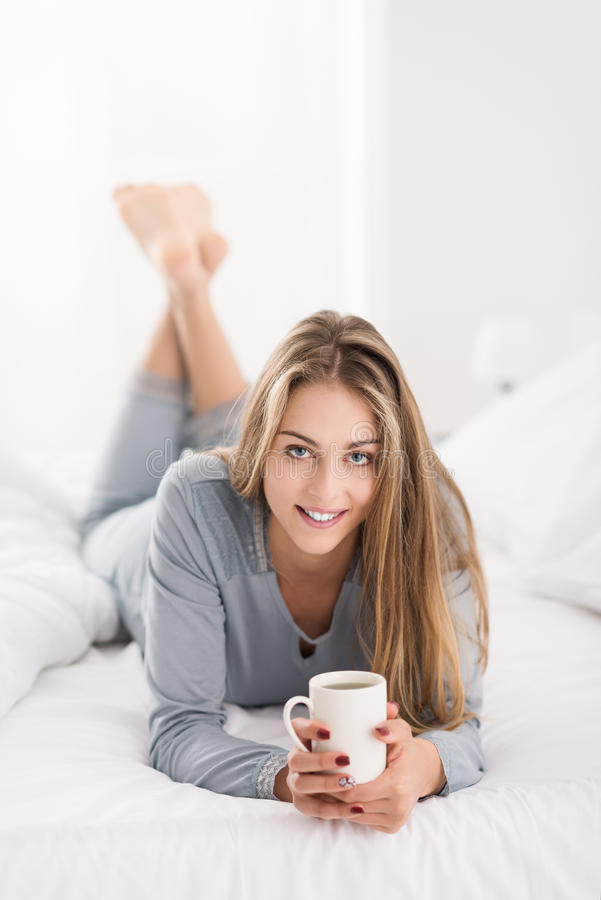 Giovane donna attraente che si siede nel suo letto fotografie stock libere da diritti