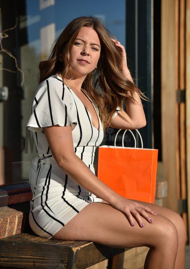 Giovane donna attraente che si siede su un banco fotografie stock libere da diritti