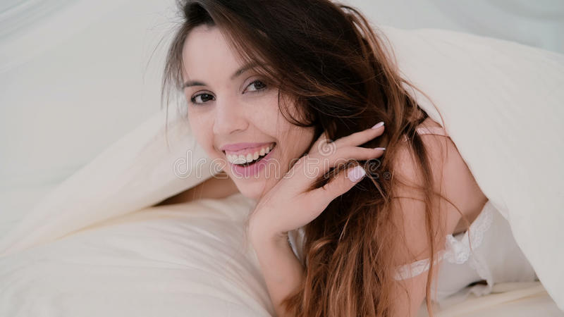 Giovane donna attraente che si trova nel letto, godente della mattina a casa Ragazza che esamina la macchina fotografica e sorrid fotografie stock